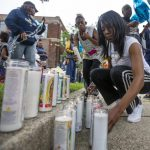 Sherika Logan lights candles for her uncle during a vigil for Eric Logan on Monday on Washington Street in South Bend. (Tribune Photo/MICHAEL CATERINA)