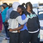 A man consoles a crying woman at the scene of a shooting in the 300 block of North O'Brien Street on April 8 in South Bend, where 21-year-old Keyontae Lamarr Jones was killed.
